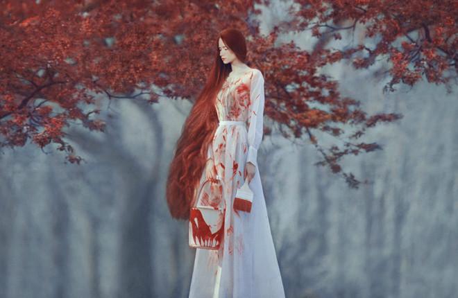 Ана. Момиче с бяла рокля, изцапано с червена боя, на фона на есенно дърво.