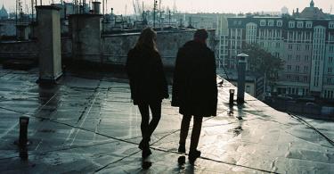 Двойка влюбени върху покрив над града.